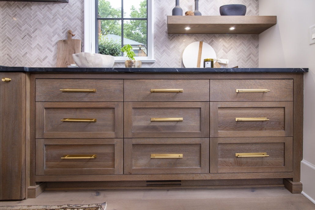 white oak kitchen cabinet drawers with brass hardware and black countertop