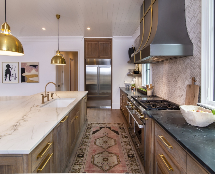 white oak kitchen cabinets with stainless steel appliances and white countertop and tile backsplash