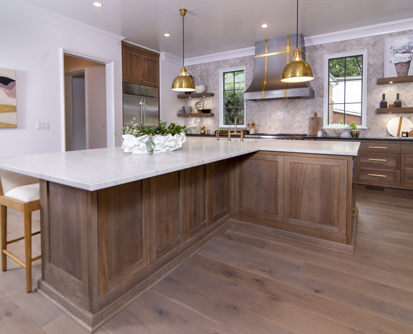White oak kitchen with t shaped kitchen island with white countertop and wood flooring