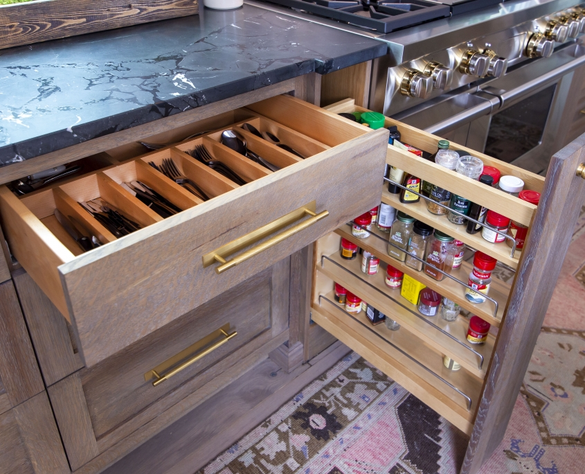 spice rack pull out in kitchen cabinet with black countertop