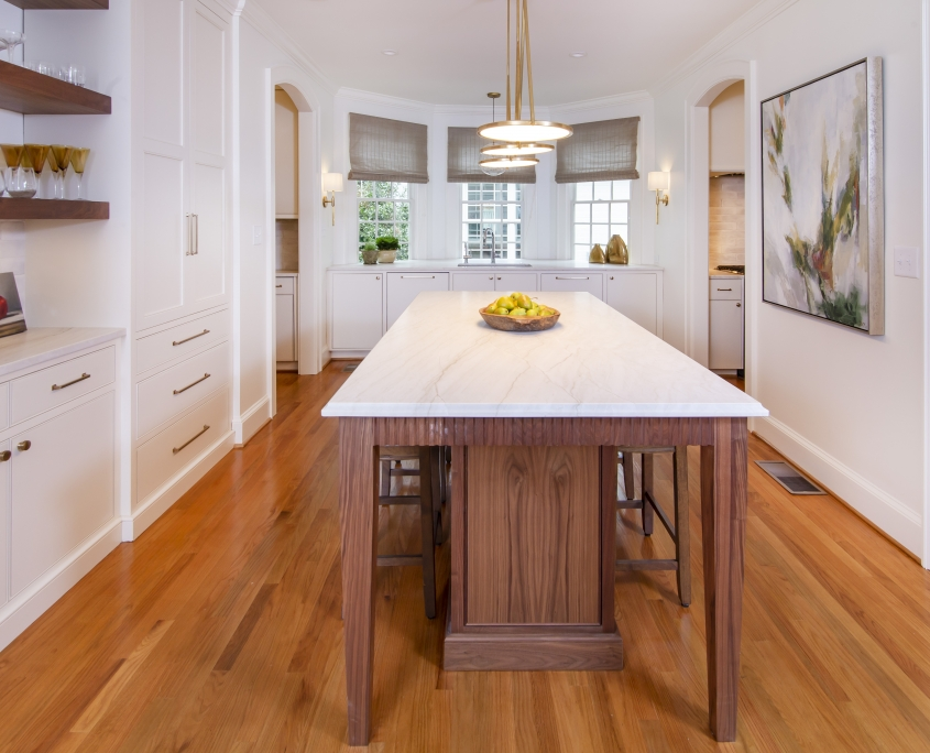 Walnut kitchen island in a white kitchen with floating shelves