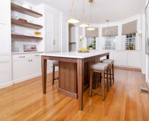 walnut kitchen island with bar stools in white kitchen with floating shelves