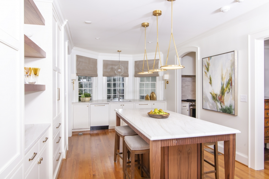 white kitchen with walnut island and white countertop and brass light fixtures