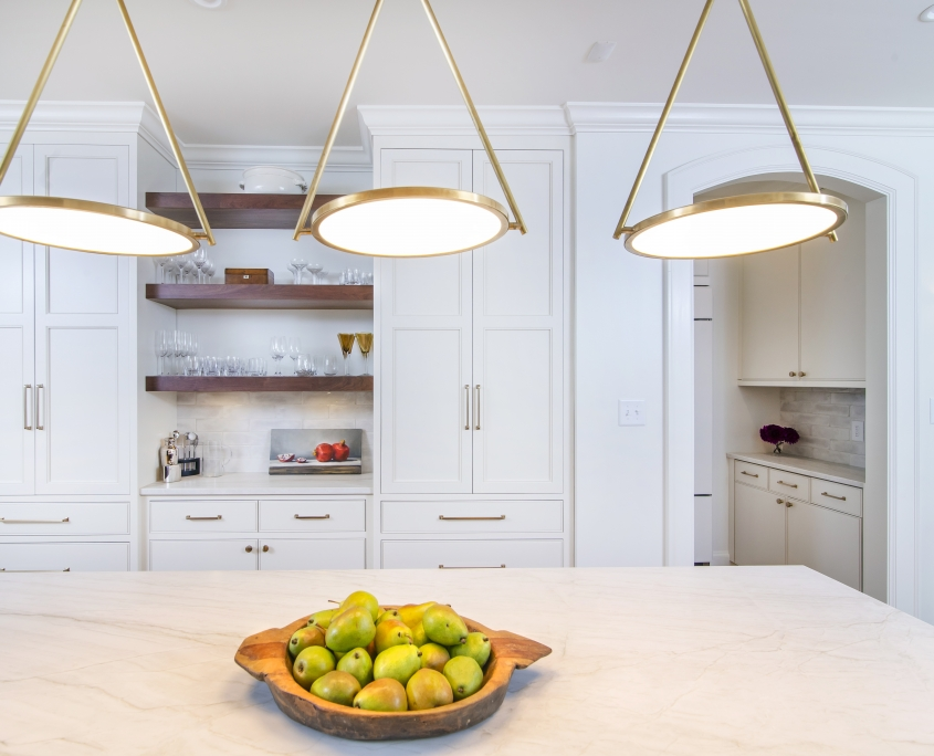 white kitchen cabinets with brass light fixtures and white countertop