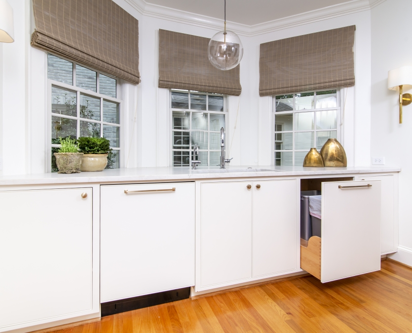 Bay window with white kitchen cabinets and trash can pull-out