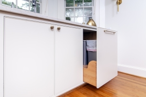white kitchen cabinets with trash can pull-out by the bay window