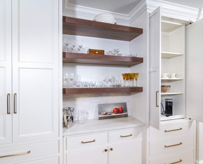 White kitchen cabinets with pocket doors. Floating walnut shelves