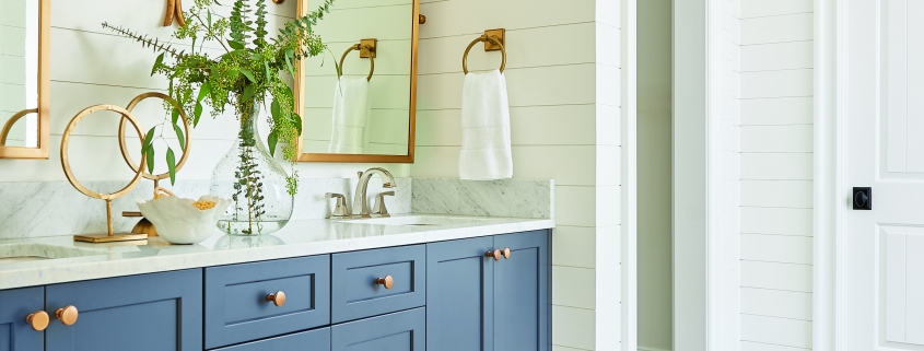 white and blue master bathroom with double sink and white shiplap walls and gold framed mirrors
