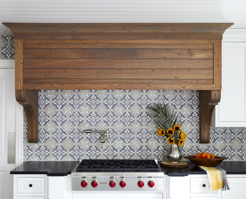 custom range wood hood from quarter sawn white oak and surrounded by white kitchen cabinets and tile backsplash