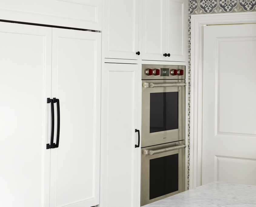 white kitchen cabinets with double wall oven and black hardware