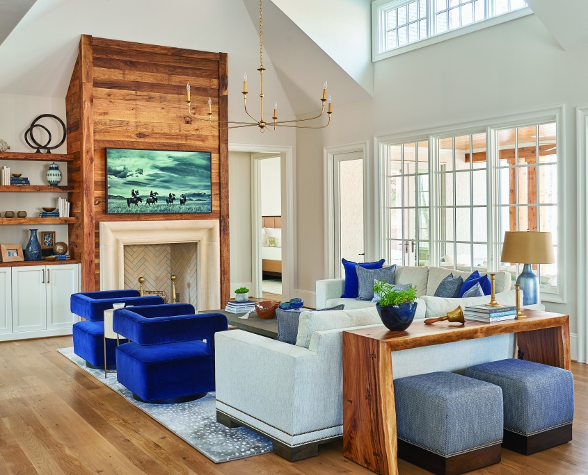 rustic modern family room with vaulted ceilings, floating shelves, white cabinets and blue chairs