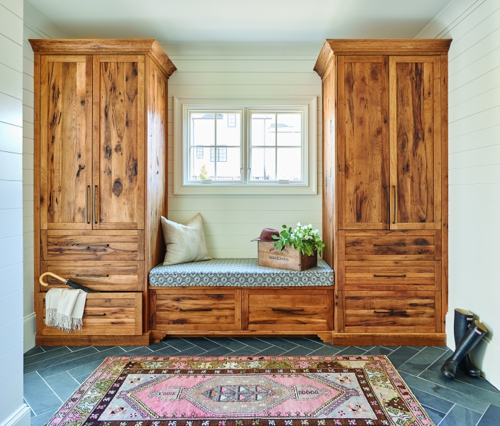 Farmhouse mudroom with wood bench seating and two large storage cabinets with drawers