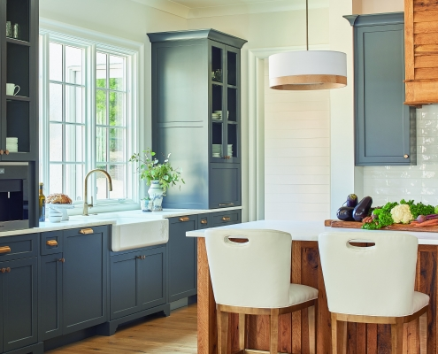 modern farmhouse kitchen with apron sink and reclaimed wood kitchen island and large window framed by large blue gray cabinets