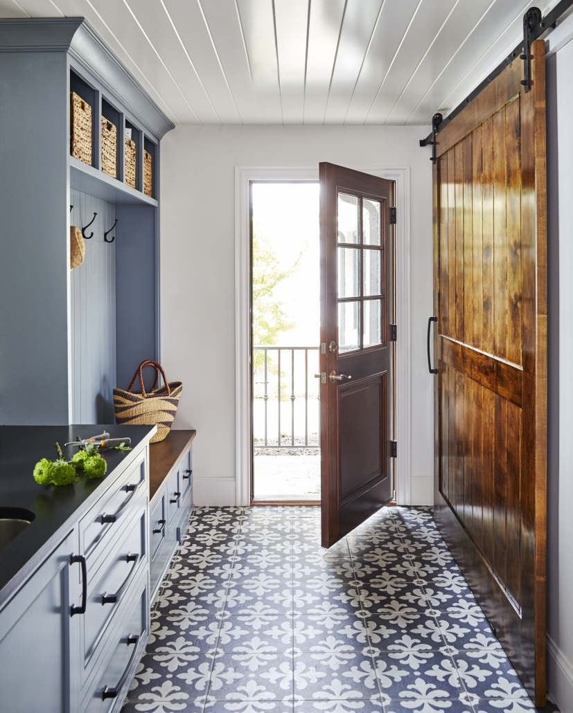 mudroom rear entry way with sliding barn door and tile flooring and blue gray cabinets and black countertop