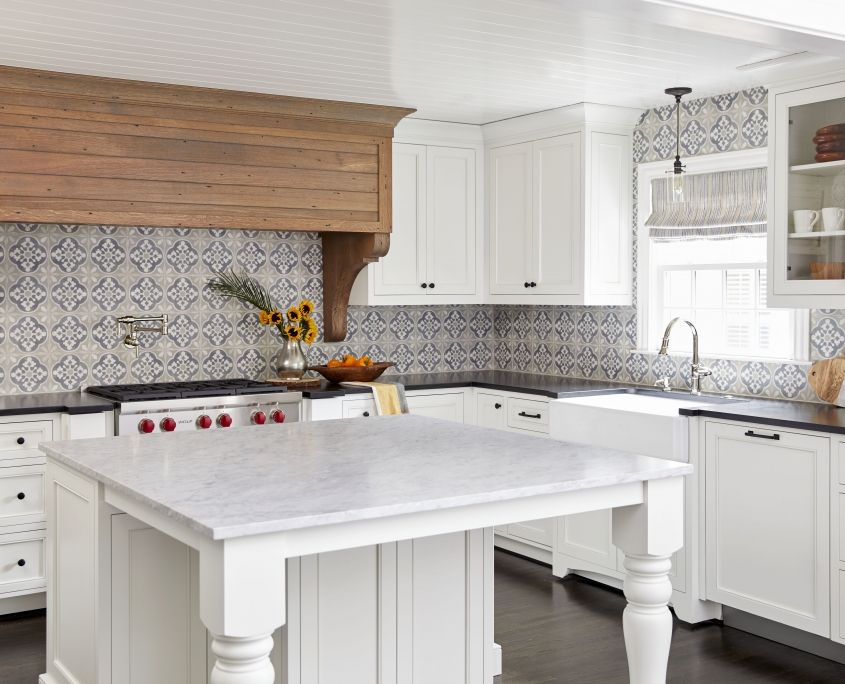 Traditional white kitchen cabinets with kitchen island and white countertops plus a custom wood range hood and black countertops and black hardware